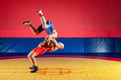 Two Strong Wrestlers In Blue And Red Wrestling Tights Are Wrestlng And Making A Suplex Wrestling On  poster