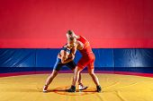 The Concept Of Fair Wrestling. Two Greco-roman  Wrestlers In Red And Blue Uniform Wrestling  On A Ye poster