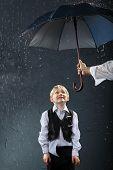 smiling boy dressed in white shirt and black vest standing under umbrella in rain; man hand holds um