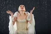 stock photo of jupe  - beautiful girl wearing in dress with corset freezes in rain and catches drops by hands - JPG