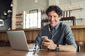 Portrait of businessman using smartphone with earphones and laptop. Smiling business man sitting in  poster