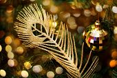 Glitter Golden Feather Against Christmas Tree Decorated With Shiny Festive Bauble Illuminated With F poster