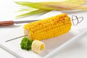 Skewer with grilled corn cob and butter curl on a tray