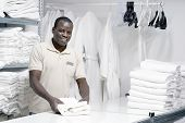 African Male Hotel Worker Folds A Clean White Towel. Hotel Staff Workers. Hotel Linen Cleaning Servi poster