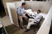zwei männlichen Kollegen arbeiten in Kabine mit Blaupausen
