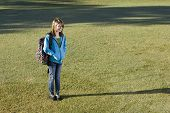 Smiling child (11 years) carrying bookbag over her shoulder, standing on grass