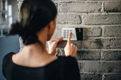 Young Woman Entering Security Pin On Home Alarm Keypad. poster