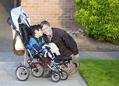 Disabled Boy In Wheelchair And His Caretaker