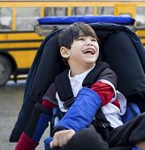 image of biracial  - Disabled five year old boy in wheelchair by schoolbus - JPG