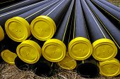 stock photo of thermoplastics  - Black plastic pipes with yellow caps and stored for assembly - JPG