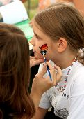 picture of face painting  - A young girl is getting her face painted with a rainbow design - JPG