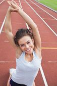 Woman on a track in a stadium stretching her arms