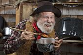 stock photo of saucepan  - Classic old western style cowboy with felt hat grey whiskers red bandana - JPG
