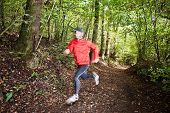 Male trail runner running in the forest on a trail. Red shirt and black pants. Summer season. Slight
