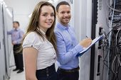 Two smiling  technicians checking the servers in data center