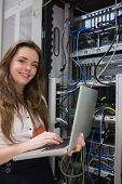 Woman happily using laptop to work on servers in data center