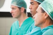Three surgeons thinking in operating theatre