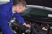 Mechanic repairing the engine with a spanner in a garage
