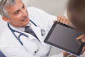 Doctor holding a tablet computer while looking at a patient in medical office