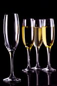 Three full glasses of champagne and one empty against black background