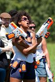 Woman Defiantly Brandishes Weapons Just Before Water Gun Fight