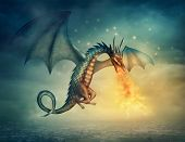 stock photo of fire-breathing  - Flying fantasy dragon with  fire at night - JPG