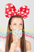 Young woman with colorful lollipop and big dotty bow