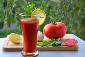 stock photo of mary  - Glass of Bloody Mary cocktail and ingredients on chopping board in the garden - JPG