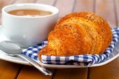 Croissant With Marmalade And Caffee Cup. On Wooden Backgroun