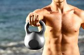 Crossfit fitness man training with kettlebells outtside. Kettlebell closeup of fit male sport athlete strength training shoulder and arms outdoors on beach.