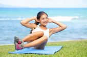 Fitness woman exercising sit ups outside during crossfit exercise training. Happy fit girl doing side crunches with elevated legs while smiling happy. Beautiful mixed race Asian female model.