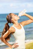 Fitness woman drinking water after running at beach. Thirsty sport runner resting taking a break wit