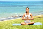 Yoga woman meditating woman relaxing by ocean sea doing the Sukhasana, easy pose. Woman in meditatio