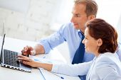smiling businesswoman and businessman working with laptop in office
