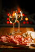 Platter of serrano jamon Cured Meat with cozy fireplace and wine background