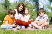 teacher reads a book to children in a summer park