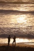 A couple talking at sunset on the sea shore at the famous surfing beach Fistral Bay, Cornwall, UK