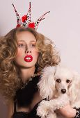 Young fashionable queen with crown and mantle with dog