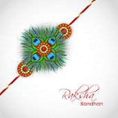 Beautiful rakhi design decorated with peacock feather on grey background on the occasion of Happy Ra