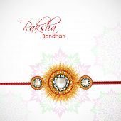 Beautiful rakhi on floral decorated grey background on the occasion of Happy Raksha Bandhan festival