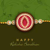 Beautiful Rakhi on floral decorated green and brown background on the occasion of Happy Raksha Bandh