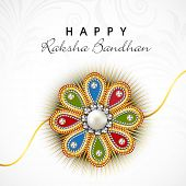 Colorful floral decorated rakhi on floral decorated grey background for the festival of Raksha Bandh