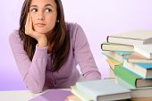 Student girl looking aside sitting behind stack of books purple