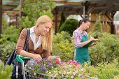 Young woman shopping cart for flowers at garden center smiling