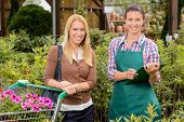 Customer and worker in garden center shopping flowers smiling portrait