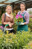 Customer and employee in garden center hold potted flower smiling