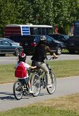 image of tandem bicycle  - mother and daughter on tanem bike in Stanley park on a nice summer day - JPG