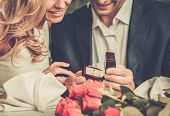 stock photo of lunch box  - Man holding box with ring making propose to his girlfriend - JPG