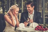 stock photo of love-making  - Man holding box with ring making propose to his girlfriend - JPG