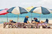 PHU QUOC, VIETNAM - APRIL 21, 2014: Beach masseuses resting  waiting of tourists in the shade of umb